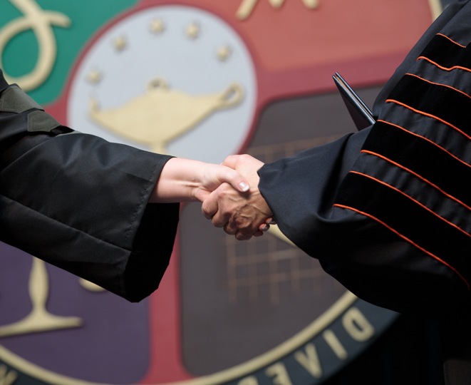 Handshake in front to the ONU University seal