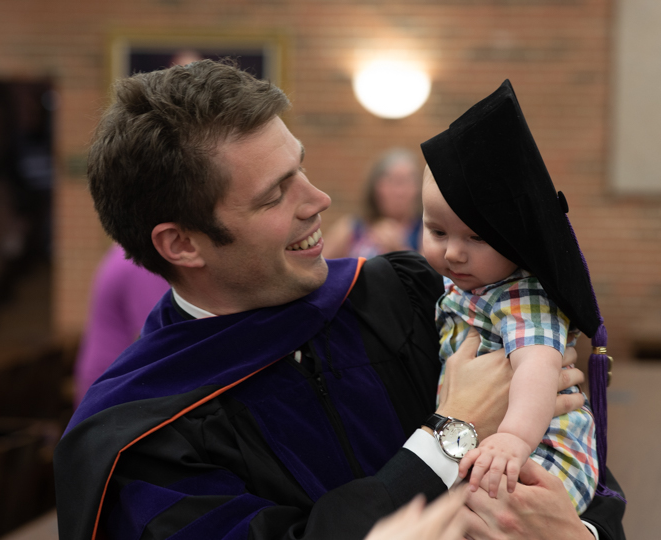 法 graduate holding his child following ceremony